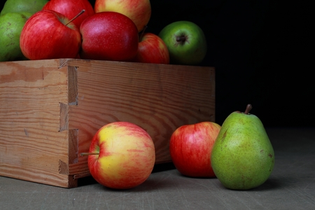Fresh autumn fruits in wooden box. Apples and pears.