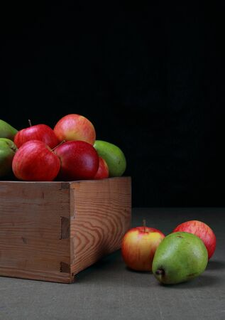 Red apples and green pears in wooden box on a black bakcground Stock Photo