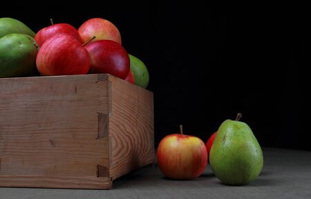 Pears and apples in a wooden box. Fruits on a black background. Stock Photo