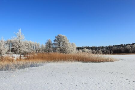 Winter landscape with beautiful frost on trees and frozen lake Stock Photo
