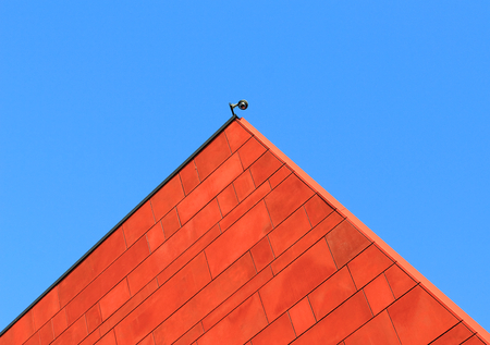 Architecture. Red wall over a blue sky. Security camera on the top Editorial
