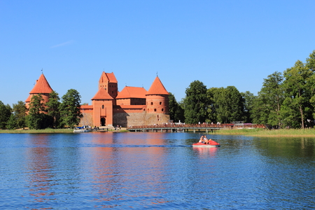 Trakai Island Castle with stone walls and towers with red tiled roofs in Lake Galve, Lithuania Stock Photo