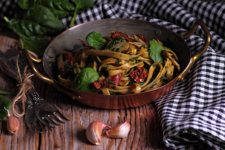 Spaghetti with spinach and dried tomatoes on a wooden table. Selective focus.