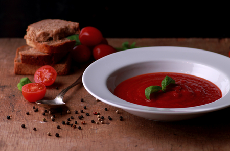 White plate with fresh tomato soup on wooden table