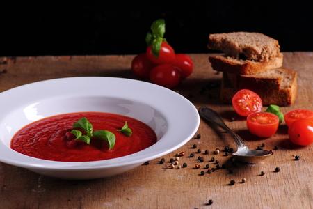 Tomato cream soup on wooden kitchen table
