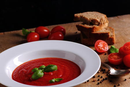 Tasty traditional tomato soup on wooden table