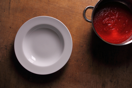 Empty plate on wooden table with fresh tomato soup Reklamní fotografie