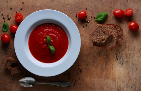 Plate with fresh tomato soup with basil