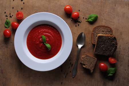 Plate with tasty tomato soup with basil