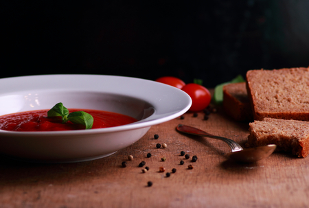 Tomato soup with basil on wooden table