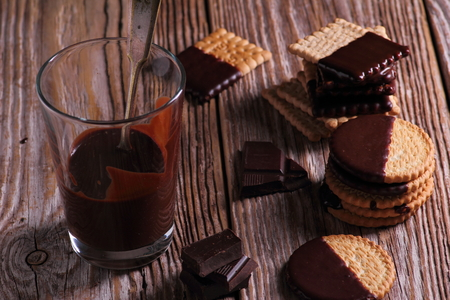 Glass with chocolate and sweet milky biscuits
