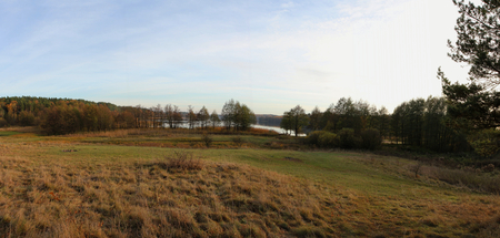 Rural landscape. Panoramic view on lake and forest in autumn.