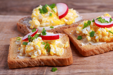 Toasted bread with scrambled eggs with fresh chives and radish for breakfast Zdjęcie Seryjne