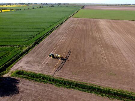 Tractor with sprayer machine working in fields, Zulawy Wislane, Poland Standard-Bild - 148688832