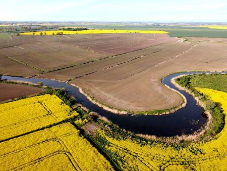 River flowing among rapeseed fields on Zulawy Wislane, Poland