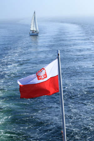 Polish flag waving on the mast of a ship at sea with a yacht in the background