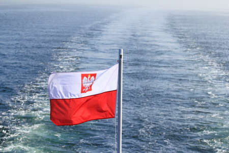 Polish flag waving while sailing on a yacht in the sea