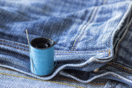 The spool of thread, needle, old jeans