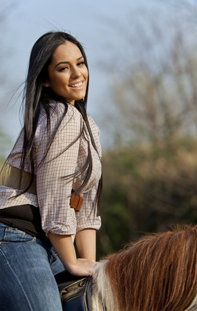 Young girl riding on the horse photo
