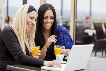 cafe internet: Chicas j�venes con ordenador port�til en el restaurante