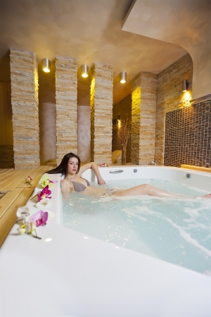 Young girl relaxing in the hot tub photo