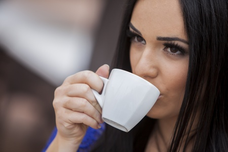 Young girl drinking coffee in restaurant photo