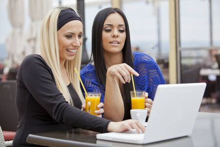 Young girls with laptop in restaurant photo