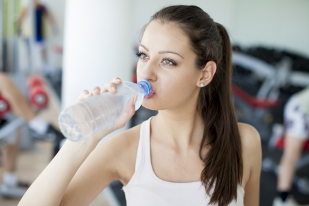 Young girl drinking water in the gym photo