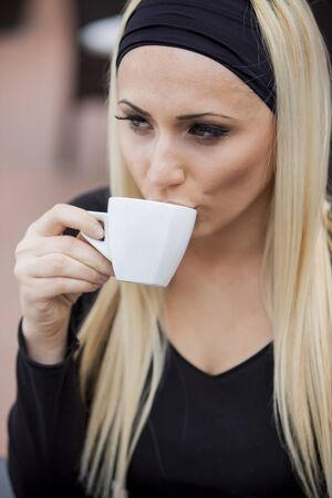 Young woman drinking coffee in restaurant photo