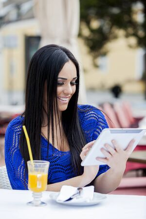 Young woman with tablet in restaurant photo