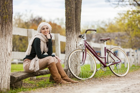 Young woman with bicycle at countryside photo