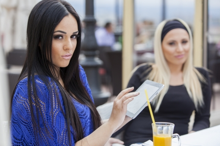 Young women with tablet in restaurant photo