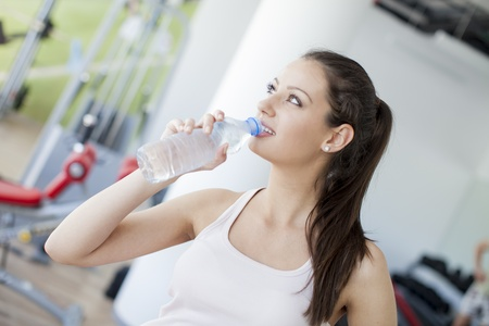 girl drinking water: Young girl drinking water in the gym