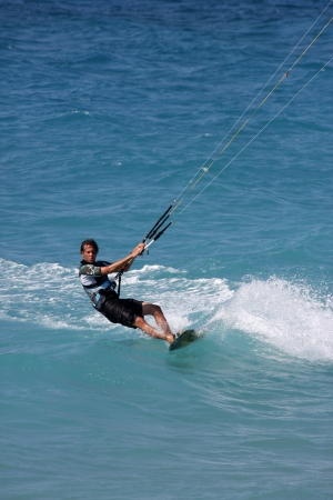 enabling: RHODES, GREECE - AUGUST 4: Unindentified man kitesurfing near Rhodes City, Greece at August 4, 2009. Constant wind from May to October enabling perfect conditions for kitesurfing on Rhodes Island.