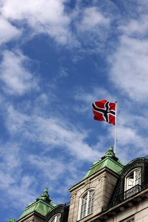 Building in Oslo, Norway with norwegian flag on the roof photo