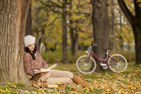 Young woman reading a book in the autumn forest photo
