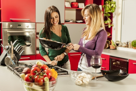 Young women in the kitchen Imagens