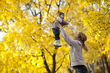 Mother and baby girl in the autumn forest photo