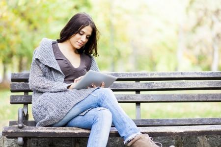 banc de parc: Jeune femme avec une tablette dans le parc