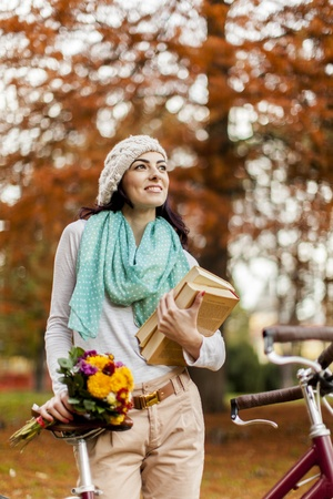 Young woman with books in the autumn forest photo