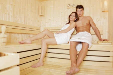woman in towel: Young couple relaxing in the sauna Stock Photo