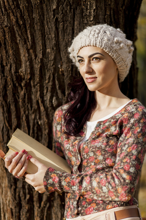 Young woman reading in the forest photo