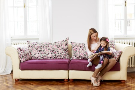 woman reading book: Mother and daughter reading in the room