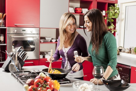 gezond koken: Young women in the kitchen Stockfoto