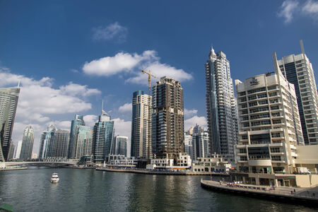 accommodate: DUBAI, UAE - JANUARY 16, 2014: View at modern skyscrapers in Dubai Marina in Dubai, UAE. When the entire development is complete, it will accommodate more than 120,000 people. Editorial