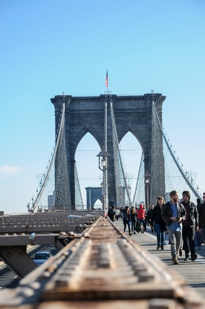 boroughs: Unidentified people crossing the Brooklyn bridge in New York at November 24, 2011. Bridge was completed in 1883, and connects the boroughs of Manhattan and Brooklyn.