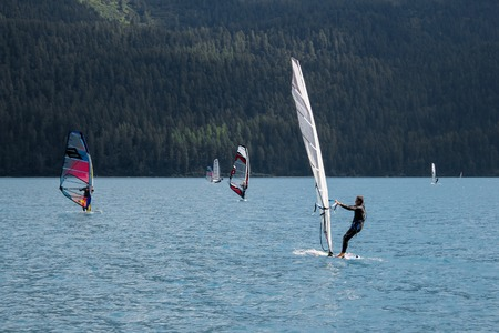 predictable: Unidentified windsurfers at Lake Silvaplana in Switzerland at August 5, 2013. Lake have a predictable winds and is popular venue for windsurfing and kitesurfing