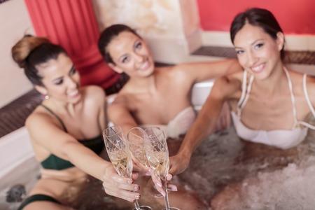 tub: Las mujeres j�venes de relax en el jacuzzi Foto de archivo