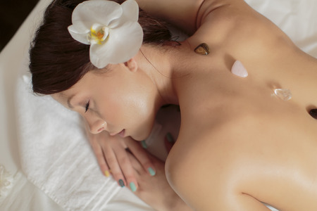 spirituality therapy:    Beautiful woman getting Crystal therapy treatment   Stock Photo