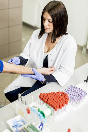 Young woman doing blood sampling in modern medical laboratory photo